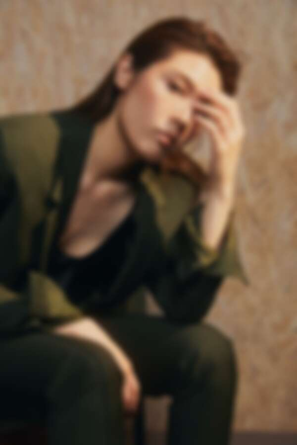 墨綠色混紡西裝外套、細肩帶上衣、墨綠色混紡長褲、皮革尖頭低跟鞋,all by Bottega Veneta。