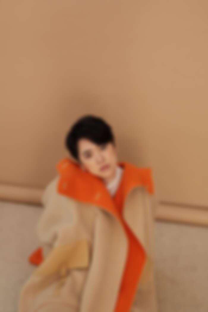 白高領透膚上衣 LOEWE;雙色駱駝斗篷大衣、米色馬褲、小牛皮長靴All by HERMÈS;幾何金耳扣、圓圈線條耳扣、圈形金耳環、字母線條戒指、金色戒指All by APM MONACO。