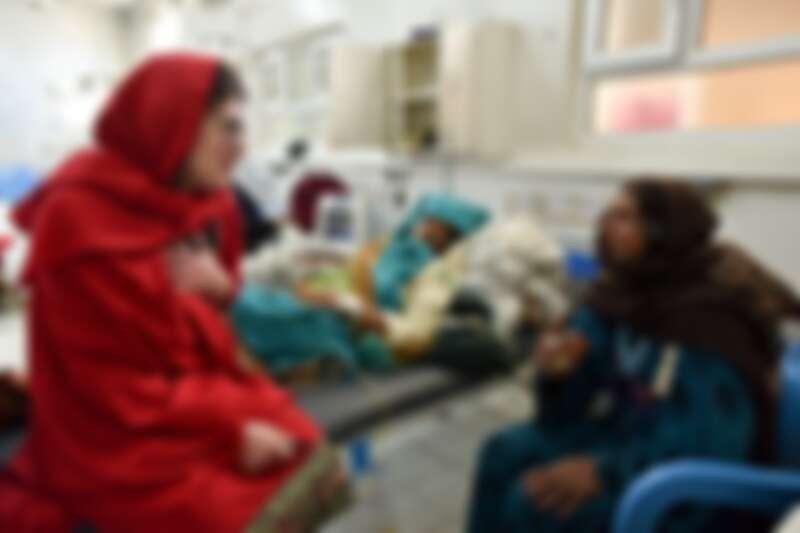 一位MSF婦產科醫生兼婦女健康顧問與一對患者母女聊天,女兒五天前在家中產後大出血,目前正逐漸復原。© Najiba Noori