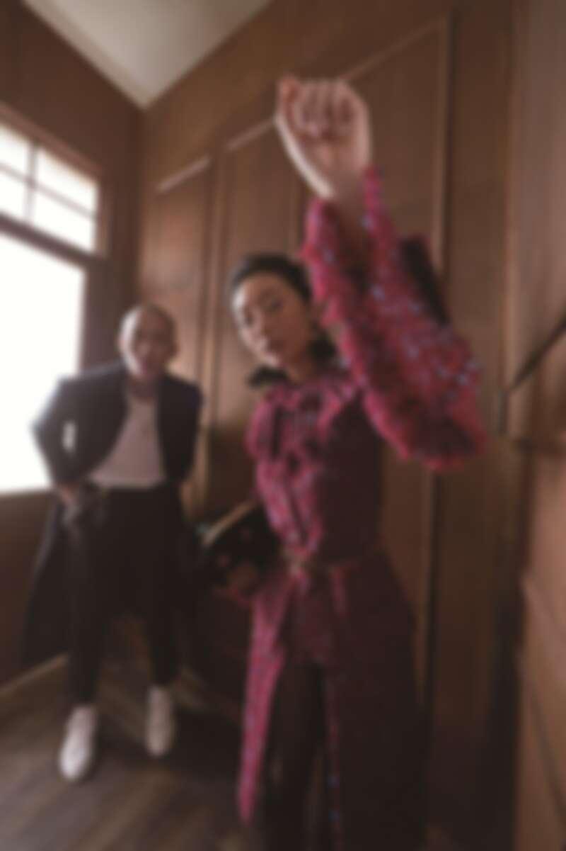 女:紫紅色亮片刺繡斜紋軟呢套裝、十字造型多彩寶石高級樹酯腰鍊、黑色絨布多彩寶石鑲飾手拿包,Chanel。男:黑色拼接亮片刺繡斜紋軟呢長外套、金屬雙C Logo項鍊,CHANEL。