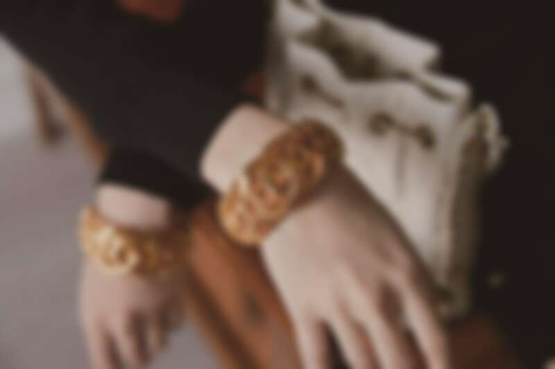 黑白拼接蕾絲緄邊洋裝、黑色十字造型高級樹脂手環、白色菱格紋皮革穿金屬鍊帶水桶包,CHANEL。