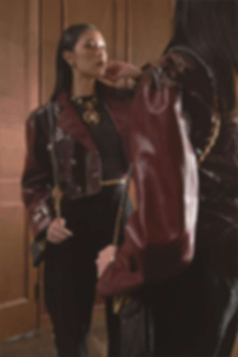 勃根地紅皮革短外套、圖紋印花上衣、黑色絲絨吸釦馬褲、馬爾他十字造型皮穿項鍊、雙C Logo金屬耳環、黑色菱格紋CHANEL 19手機包、水晶鑲飾樹酯金屬腰鍊,CHANEL。