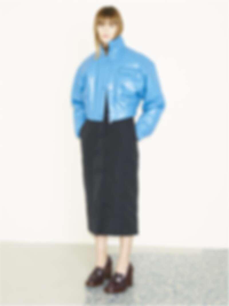 寶藍色皮革落肩外套、深色裙裝、深咖啡色高跟樂福鞋,all by Tod's。